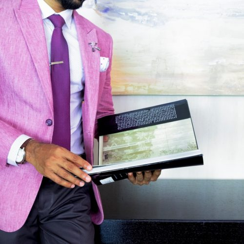 man-in-pink-suit-jacket-holding-book-2247181